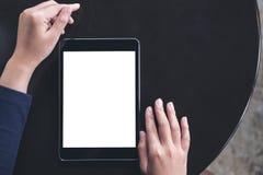 Изображение модель-макета женщины используя черный ПК таблетки с пустым белым экраном Стоковое фото RF