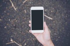 Изображение модель-макета руки ` s женщины держа белый мобильный телефон с пустым черным экраном Стоковое Изображение