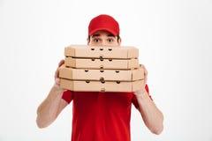 Изображение молодого работника доставляющего покупки на дом в красной стороне заволакивания футболки и крышки Стоковое Фото