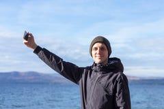 Изображение молодого человека принимая selfie с его телефоном стоковые изображения rf