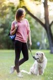Изображение молодой женщины на прогулке с собакой в парке лета Стоковая Фотография RF