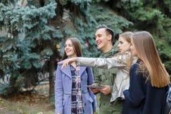 Изображение молодых друзей outdoors с компьютером в руках молодого человека стоковые изображения rf