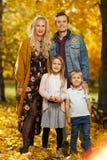 Изображение молодых родителей и детей на прогулке в парке осени стоковое изображение rf
