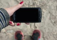 Изображение модель-макета положения вниз и руки держа черный мобильный телефон с пустым экраном на предпосылке песка Стоковые Фото