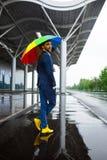 Изображение молодого бизнесмена в желтых ботинках держа пестрый зонтик в ненастной улице Стоковая Фотография