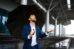 Изображение молодого бизнесмена держа зонтик в дожде смотря вверх на падениях Стоковое Фото
