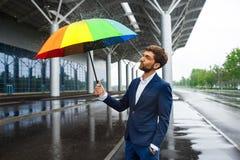 Изображение молодого бизнесмена держа красочный зонтик с брызгает вокруг в ненастной улице Стоковое Фото