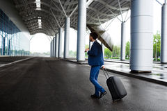 Изображение молодого бизнесмена держа чемодан и зонтик на ненастном стержне Стоковое Фото