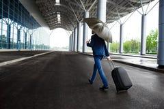 Изображение молодого бизнесмена держа чемодан и зонтик на ненастном стержне Стоковые Изображения RF