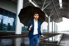 Изображение молодого бизнесмена держа чемодан и зонтик стоя на ненастной станции смотря в камере Стоковая Фотография
