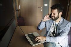 Изображение молодого успешного бизнесмена говоря на телефоне и используя компьтер-книжку Стоковые Изображения
