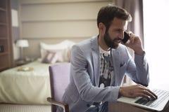Изображение молодого успешного бизнесмена говоря на телефоне и используя компьтер-книжку Стоковые Изображения RF