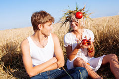 Изображение молодого человека и женщины с яблоками на пшеничном поле Стоковые Изображения RF