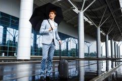 Изображение молодого redhaired бизнесмена держа черные зонтик и чемодан в дожде на авиапорте Стоковые Фото