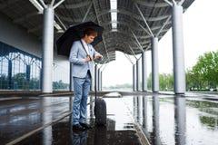 Изображение молодого redhaired бизнесмена держа черный зонтик в дожде и смотря на вахте Стоковое Фото