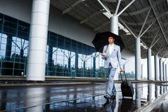 Изображение молодого redhaired бизнесмена держа черный зонтик и чемодан идя в дождь на станции Стоковое фото RF