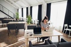 Изображение молодой красивой женщины сидя на таблице с портативным компьютером и держа smartphone, пока ее ассистент Стоковые Изображения