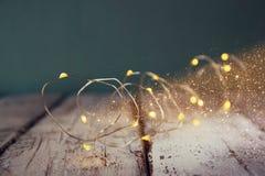 Изображение низкого ключа и селективного фокуса гирлянды золота рождества теплой освещает на деревянной деревенской предпосылке Стоковое Изображение RF
