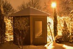 Изображение ночи округленного дома сада в зимнем времени покрытом снегом и освещенном уличным фонарем с оранжевым светом Стоковое фото RF
