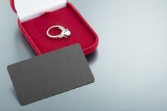 Изображение обручального кольца в красной подарочной коробке на серой предпосылке Стоковые Изображения