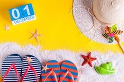 Изображение 1-ое декабря календаря 1-ое декабря с аксессуарами пляжа лета и обмундированием путешественника на предпосылке Зима л Стоковое Изображение