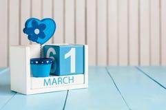 Изображение 1-ое марта календаря цвета 1-ое марта деревянного с цветком и сердца на белой предпосылке Первый весенний день, пусто Стоковое фото RF