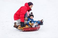 Изображение отца, сына, дочерей ехать трубопровод в парке зимы стоковая фотография rf