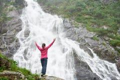 Изображение от задней части женский туристский подниматься вручает вверх по наслаждаться красивым захватывающим взглядом водопада Стоковые Изображения