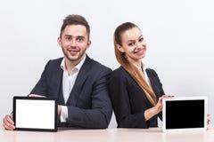 Изображение пар работников офиса оба держа таблетку Стоковая Фотография RF