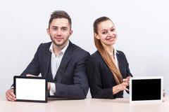 Изображение пар работников офиса оба держа таблетку Стоковое фото RF