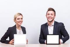 Изображение пар работников офиса оба держа таблетку Стоковая Фотография