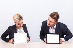 Изображение пар работников офиса оба держа таблетку Стоковые Изображения RF
