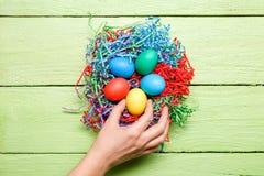 Изображение пестротканых пасхальных яя и руки на зеленой деревянной предпосылке Стоковые Изображения