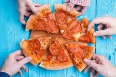 Изображение пиццы на таблице Части взятия людей Стоковое Изображение