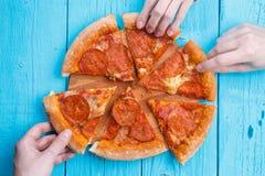 Изображение пиццы на таблице b Куски взятия людей Стоковое Изображение RF