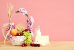 Изображение плодоовощей и сыра в декоративной корзине с цветками над деревянным столом Символы еврейского праздника - Shavuot стоковые изображения