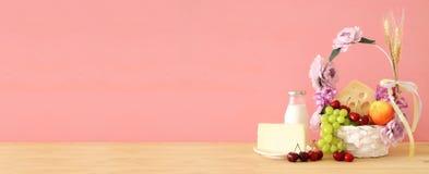 Изображение плодоовощей и сыра в декоративной корзине с цветками над деревянным столом Символы еврейского праздника - Shavuot стоковое изображение