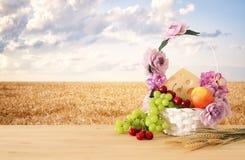 Изображение плодоовощей и сыра в декоративной корзине с цветками над деревянным столом Символы еврейского праздника - Shavuot стоковые фотографии rf