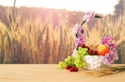 Изображение плодоовощей и сыра в декоративной корзине с цветками над деревянным столом Символы еврейского праздника - Shavuot стоковые фото