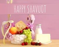 Изображение плодоовощей и сыра в декоративной корзине с цветками над деревянным столом Символы еврейского праздника - Shavuot стоковое изображение rf
