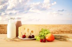 Изображение плодоовощей и сыра в декоративной корзине с цветками над деревянным столом Символы еврейского праздника - Shavuot стоковая фотография rf