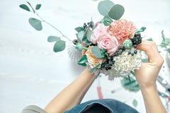 Изображение подрезанное взглядом сверху женского флориста аранжируя букет с цветками использует инструменты на белой предпосылке  стоковое фото rf