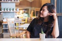 Изображение портрета крупного плана женщины smiley красивой азиатской с чувствовать хороший сидеть и ослаблять в кафе с малым бак Стоковые Изображения