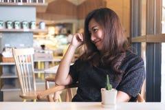 Изображение портрета крупного плана женщины smiley красивой азиатской с чувствовать хороший сидеть и ослаблять в кафе Стоковая Фотография RF