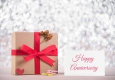 Изображение подарочной коробки с красное anniversar ленты и сообщения счастливое Стоковые Фото