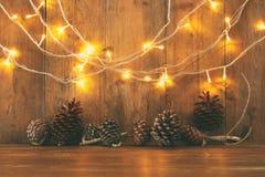 Изображение праздника с светами гирлянды рождества золотыми и конусами сосны над деревянной предпосылкой Стоковые Изображения RF