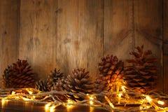 Изображение праздника с светами гирлянды рождества золотыми и конусами сосны над деревянной предпосылкой Стоковое Изображение RF