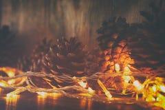 Изображение праздника с светами гирлянды рождества золотыми и конусами сосны над деревянной предпосылкой Стоковые Изображения