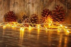 Изображение праздника с светами гирлянды рождества золотыми и конусами сосны над деревянной предпосылкой Стоковое Фото