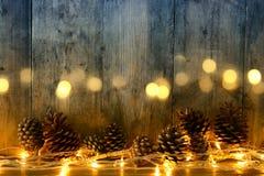 Изображение праздника с светами гирлянды рождества золотыми и конусами сосны над деревянной предпосылкой Стоковые Фото
